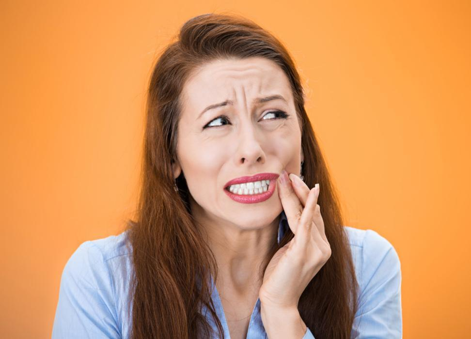 Woman holding jaw from pain | Calgary AB Dentist
