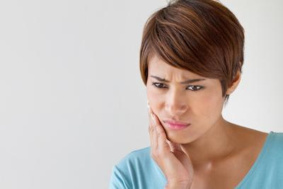 Woman holding jaw | Calgary AB Emergency Dentist