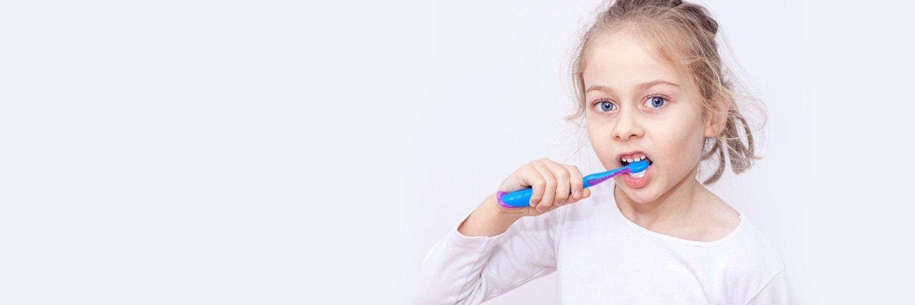 Child holding toothbrush | Dentist Calgary AB